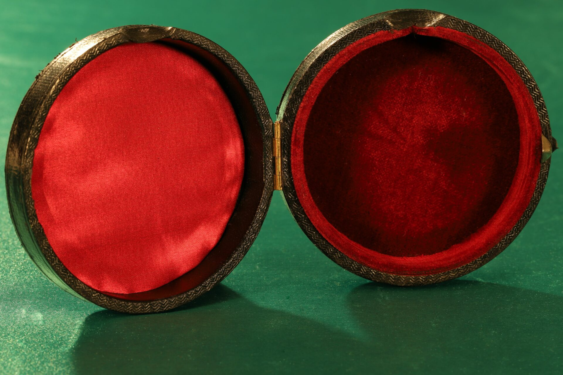 Image of interior of the travel case for French Scientific Pocket Barometer Altimeter c1890, showing the red silk in the inner top half, and the deeper red velvet in the bottom half