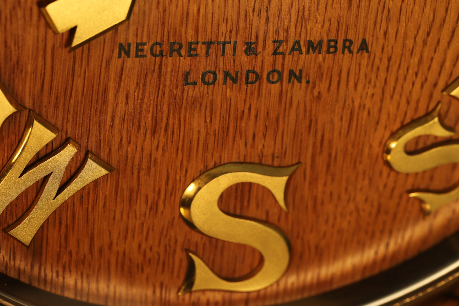 A front shot close up of the lower part of a substantial and beautiful Negretti & Zambra wind indicator, showing the signature