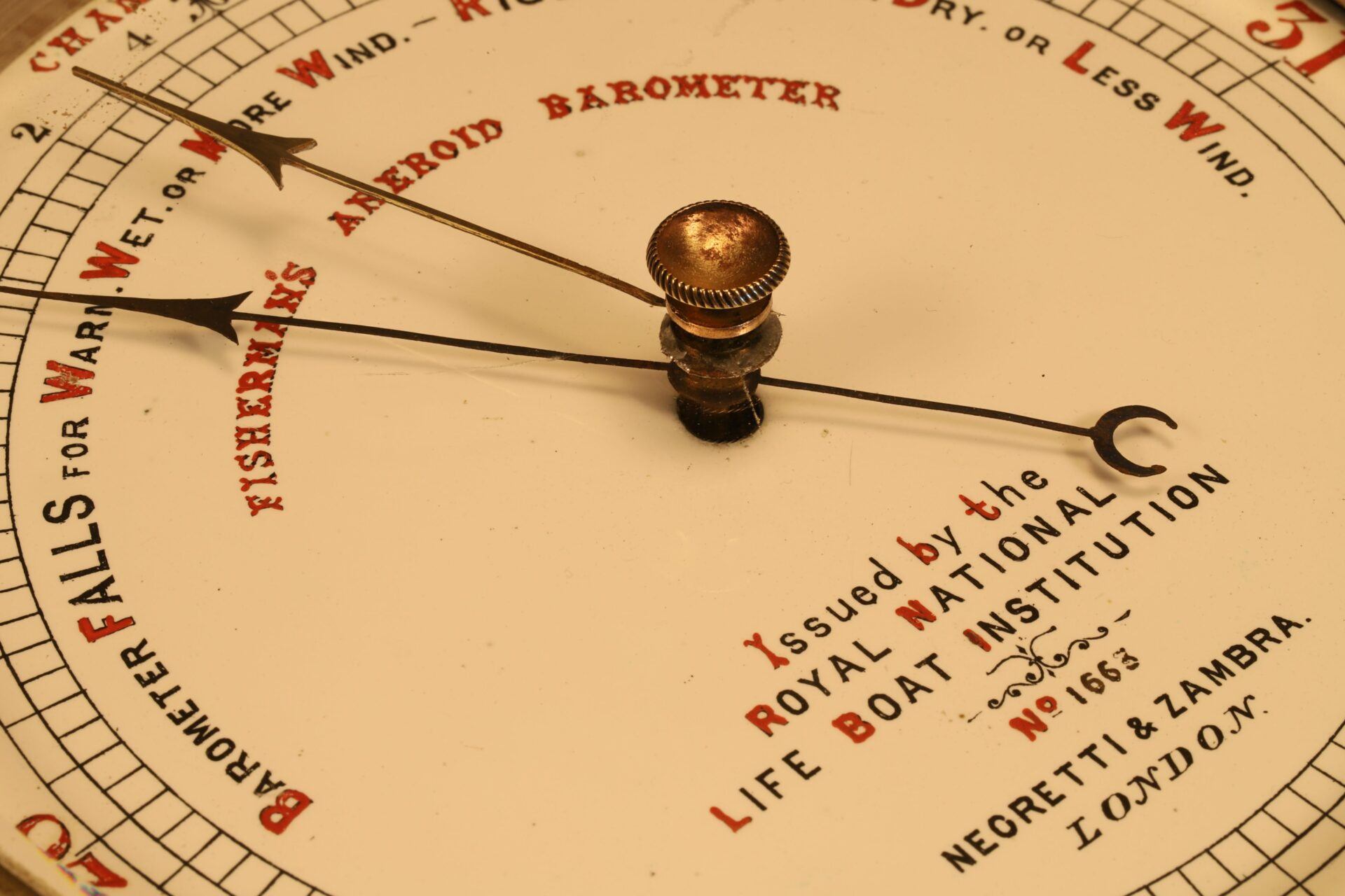 Close up of dial from Negretti & Zambra RNLI Fishermans Aneroid Barometer No 1663 showing pointer and telltale taken from lefthand side