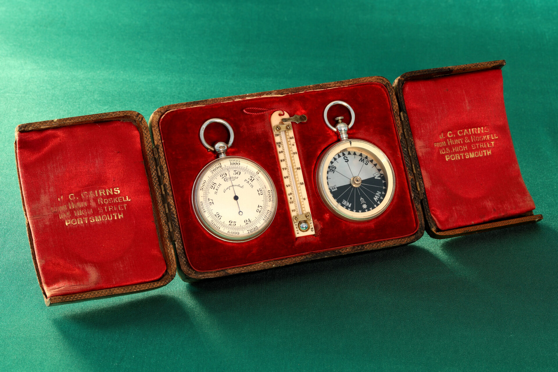 Image of open case from Cairns Silver Pocket Barometer Compendium c1892 showing the retailer's details and the pocket barometer, thermometer and compass, taken from lefthand side