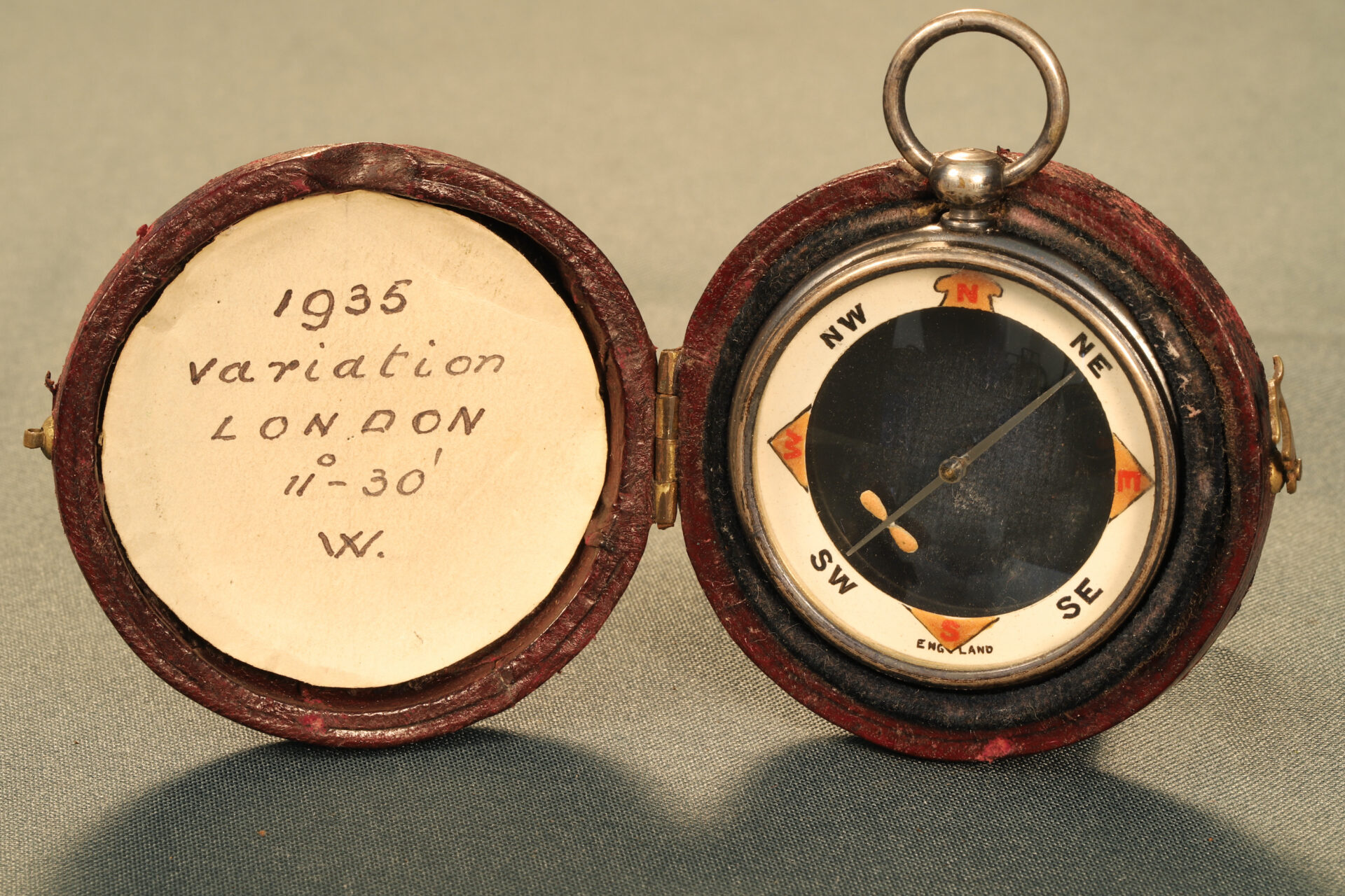 Image of front of Barker Radiant Transparent Pebble Lens Compass c1910 in travel case